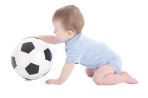 funny baby boy toddler playing with soccer ball isolated on white background